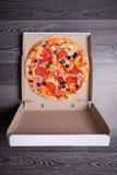 Draufsicht der italienischen Pizza mit Schinken, Tomaten und Oliven im Kasten Stockbild