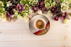 Draufsicht der Kaffeetasse über hellem hölzernem Hintergrund mit Frühlingsblumen und Osterei-Retrostilpastellfarben Lizenzfreies Stockfoto