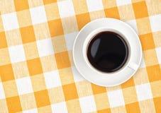 Draufsicht der Kaffeetasse auf überprüfter Tischdecke Stockbild