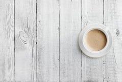 Draufsicht der Kaffeetasse über weißen hölzernen Tabellenhintergrund Lizenzfreie Stockfotografie