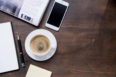 Draufsicht der Kaffeetasse, des Smartphone mit leerem Bildschirm, des Notizbuches mit Stift und der Zeitung Lizenzfreies Stockfoto