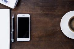 Draufsicht der Kaffeetasse, des Smartphone mit leerem Bildschirm und des Notizbuches mit Stift Stockfoto