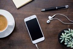 Draufsicht der Kaffeetasse, des Smartphone mit leerem Bildschirm und Kopfhörern, des Notizbuches mit Stift und der saftigen Anlag Lizenzfreie Stockfotografie