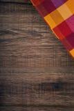 Draufsicht der karierten Serviette auf Holztisch Lizenzfreie Stockbilder