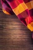 Draufsicht der karierten Serviette auf Holztisch Lizenzfreie Stockfotos