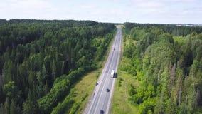 Draufsicht der Landschaftslandstraße in der Waldfläche clip Landstraße mit Verkehr von den Autos und von LKWs, die zur Stadt weit stock footage