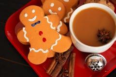 Draufsicht der Lebkuchenmänner mit Kaffee auf rotem Teller lizenzfreies stockfoto
