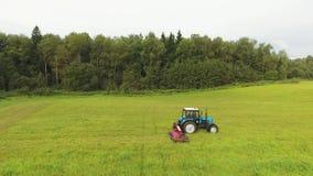 Draufsicht der mähenden Grasoberfläche des großen blauen Traktors arge gelben und grünen Feldes stock video