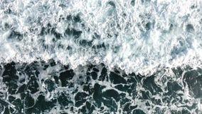 Draufsicht der Meereswogen, die gegen das felsige Ufer zusammenstoßen stockfotografie