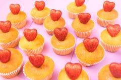 Draufsicht der Muffins mit funkelnder Draufsicht der roten Herzen tonte selektiven Fokus Stockbild