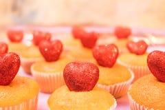 Draufsicht der Muffins mit funkelnder Seitenansicht der roten Herzen tonte selektiven Fokus Stockbild