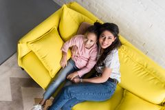 Draufsicht der Mutter und der Tochter, die zusammen auf Couch und dem Schauen sitzen lizenzfreies stockfoto