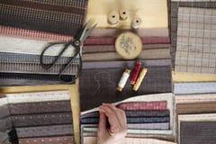 Draufsicht der nähenden Tabelle mit Geweben, Versorgungen für Hauptdekor oder steppendes Projekt und Frau ` s Hand Stockbilder