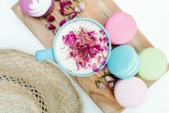 Draufsicht der Nahaufnahme über Strohhut und blaue Schale Aromacappuccino mit französischen geschmackvollen macarons Stockbilder