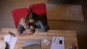 Draufsicht der Nahaufnahme der jungen kaukasischen Frau und ihrer kleinen hübschen der Tochter, die eine Karikatur auf dem Laptop stock video