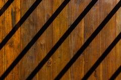 Draufsicht der Nahaufnahme von Schattenstreifen, die über dem Boden mager sind, der von hölzernem herein kreuzweise gemacht wird Stockfoto