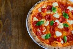 Draufsicht der neapolitanischen Pizza mit Pepperoni-, Mozzarella- und Kirschtomaten auf einem dunklen Holztisch für ein Abendesse Lizenzfreie Stockfotos