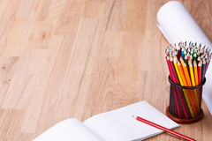 Draufsicht der Papierrolle und Schulbedarf auf dem hölzernen Hintergrund Bleistifte und Notizbuch Lizenzfreies Stockfoto