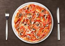 Draufsicht der Pizza über Platte mit Gabel und Messer Lizenzfreie Stockfotos