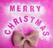 Draufsicht der Postkarte mit dem Gruß der frohen Weihnachten gemacht auf Zucker- oder Mehlpulver mit Textilbogen auf rosa Hinterg Lizenzfreies Stockbild
