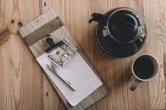 Draufsicht der Rechnung, der Barzahlung, des Glaskessels und des Tasse Kaffees auf Tischplatte im Café stockfoto