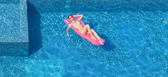 Draufsicht der schönen bräunenden Frau im Pool Stockbild