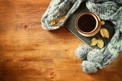 Draufsicht der Schale schwarzen Kaffees mit Herbstlaub, einem warmen Schal und altem Buch auf hölzernem Hintergrund filreted Bild Stockfoto