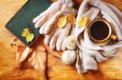 Draufsicht der Schale schwarzen Kaffees mit Herbstlaub, einem warmen Schal und altem Buch auf hölzernem Hintergrund filreted Bild Lizenzfreie Stockfotografie