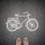 Draufsicht der Schuhe des zufälligen Mannes und ein skizziertes Modell eines Fahrrades auf Asphalt Ein Konzept der umweltfreundli Lizenzfreie Stockbilder