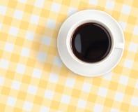 Draufsicht der schwarzen Kaffeetasse auf überprüfter Tischdecke Lizenzfreie Stockfotos