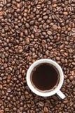 Draufsicht der schwarzen Kaffeetasse auf Kaffeebohnehintergrund Stockbilder