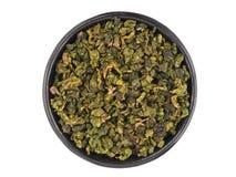 Draufsicht der schwarzen Metallschüssel mit trockenen grünen Teeblättern stockfotografie