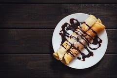 Draufsicht der selbst gemachten Pfannkuchen mit Schokoladensoße auf Platte auf dunklem rustikalem hölzernem Hintergrund, Kopienra stockfotos
