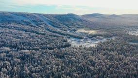 Draufsicht der Skibasis mit Steigungen auf Berg gesamtlänge Panorama von schneebedeckten Bergen mit Skisteigungen und -erholung stock footage