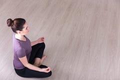 Draufsicht der sportlichen Frau sitzend in der Yogahaltung auf dem Boden lizenzfreie stockbilder