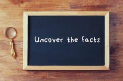 Draufsicht der Tafel mit der Phrase decken die Tatsachen auf, die auf sie nahe bei alter Lupe über Holztisch geschrieben werden Lizenzfreie Stockfotos