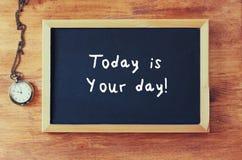 Draufsicht der Tafel mit der Phrase ist heute Ihr Tag, der auf sie nahe bei alter Uhr über Holztisch geschrieben wird Stockbilder