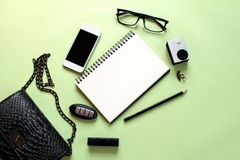 Draufsicht der Tasche der schwarzen Frau mit leerem Notizbuch, Bleistift, Lippenstift, Ohrringen, kleiner Aktionskamera, Augenglä Lizenzfreies Stockbild