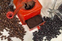 Draufsicht der traditionellen manuellen Kaffeemühle neben verschiedenen Bohnen Stockbilder