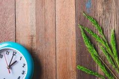Draufsicht der Uhr mit grünem ungeschältem Reis auf Holztisch Lizenzfreie Stockfotos