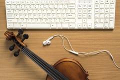 Draufsicht der Violine mit Computertastatur und -kopfhörer Stockfotografie