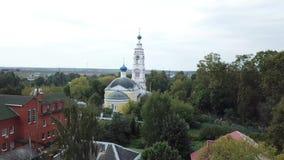 Draufsicht der weißen Kirche auf Hintergrund der Stadt im Sommer Gesamtl?nge auf Lager Panoramablick von Vororten mit Grünstreife stock footage