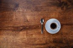 Draufsicht der weißen Schale mit schwarzem Kaffee auf einer weißen Untertasse und einem Teelöffel auf dunkelbraunem hölzernem Hin Stockfoto