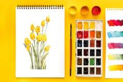 Draufsicht der Zeichnung der Blumen, der Farben, der Bürste und der bunten Pinselstriche auf Papier auf Gelb Stockfoto