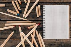 Draufsicht der Zusammensetzung der bunten Bleistifte mit leerem Notizbuch Lizenzfreie Stockfotos