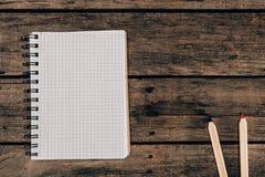 Draufsicht der Zusammensetzung der bunten Bleistifte mit leerem Notizbuch Lizenzfreies Stockbild