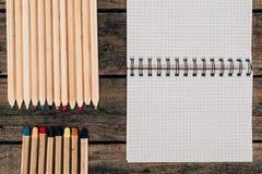 Draufsicht der Zusammensetzung der bunten Bleistifte mit leerem Notizbuch Stockfotografie