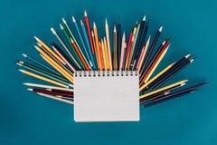 Draufsicht der Zusammensetzung der bunten Bleistifte mit leerem Notizbuch Lizenzfreies Stockfoto