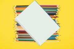 Draufsicht der Zusammensetzung der bunten Bleistifte mit leerem Notizbuch Stockbilder