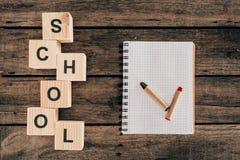 Draufsicht der Zusammensetzung der bunten Bleistifte mit leerer Notizbuch- und Wortschule Stockfotos